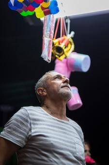 Пожилой мужчина смотрит на игрушечный киоск