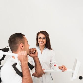 Боковой вид пациента, выполняющего упражнения под наблюдением врача