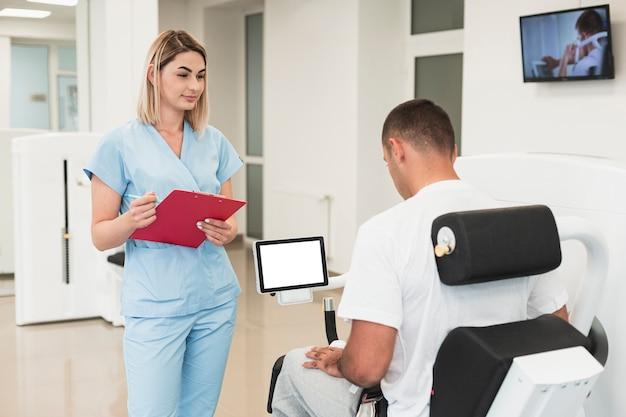 Доктор проверяет пациента, делающего медицинские упражнения