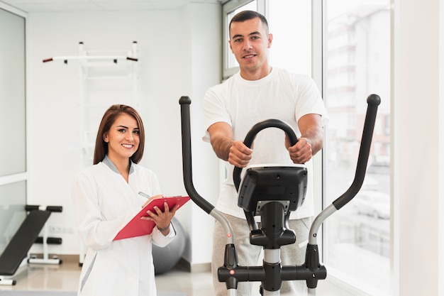 Доктор вид спереди, проверка пациента делает упражнения
