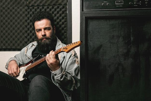 Мужчина играет на гитаре рядом с усилителем