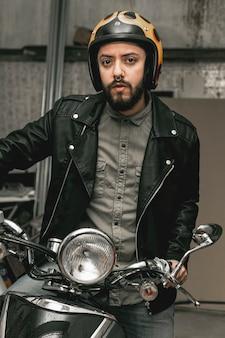 オートバイの革のジャケットを持つ男