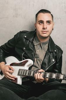 Человек играет на гитаре и смотрит в сторону