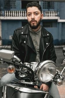 オートバイの革のジャケットを持つ正面男
