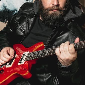 ビンテージの赤いギターを弾くひげ男