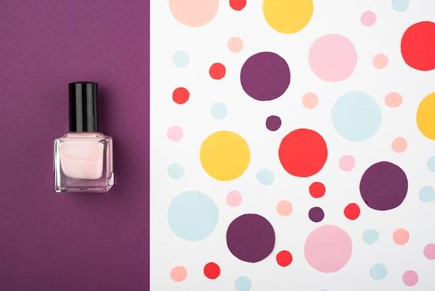 Лак для ногтей рядом с разноцветными точками