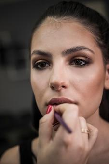 モデルに口紅を適用するメイクアップアーティスト
