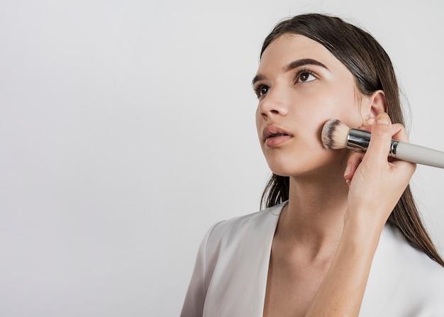 モデルのメイクアップを適用する女性