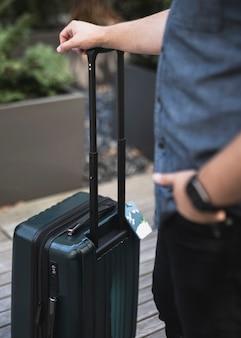 Молодой человек держит чемодан