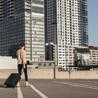 Молодая женщина гуляет с чемоданом в городе