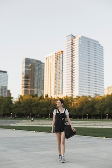 都市公園のロングショットに荷物を持つ女性