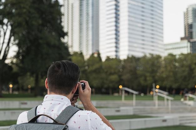 背面図若い男が写真を撮る