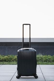 Черный чемодан сидит на тротуаре