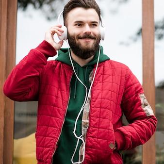 ヘッドフォンとポケットに手を持つミディアムショットの男