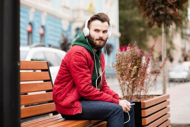 Среднего роста парень с наушниками и теплой одеждой