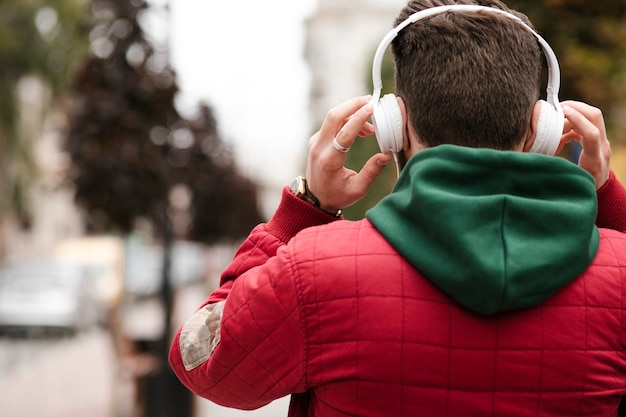 ヘッドフォンと暖かいジャケットを持つ背面図男
