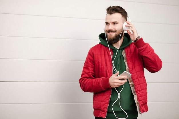 暖かい服とヘッドフォンでミディアムショットの男