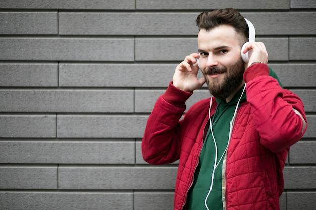 レンガの壁の近くのヘッドフォンでミディアムショットの男