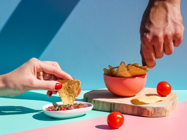 Крупным планом люди с чипсами из тортильи и соусом