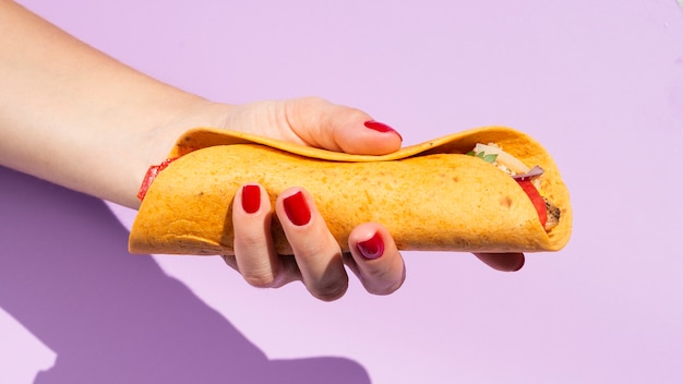 Крупный план лица с буррито и фиолетовым фоном