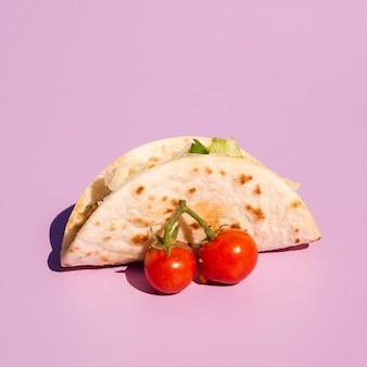 紫色の背景にタコスとチェリートマトの配置