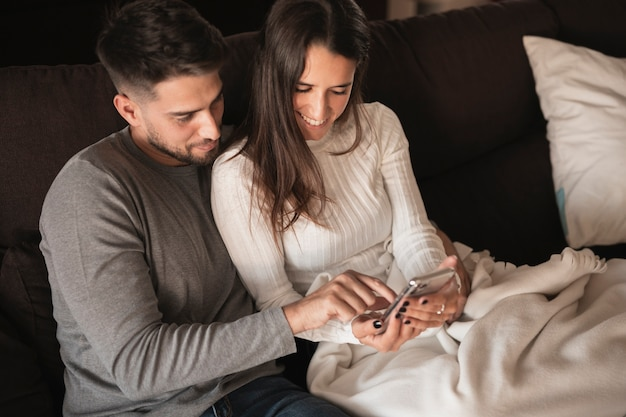 Молодая пара дома смотрит на мобильный