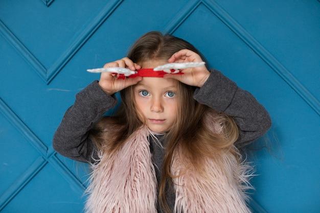 Милая маленькая девочка позирует перед синей стеной