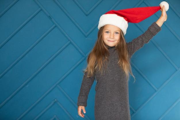 サンタクロースの帽子をかぶっている愛らしいブロンドの女の子