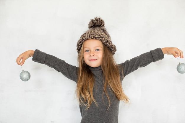 クリスマスグローブを保持しているかわいいブロンドの女の子