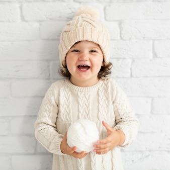 Улыбающаяся маленькая девочка держит снежок