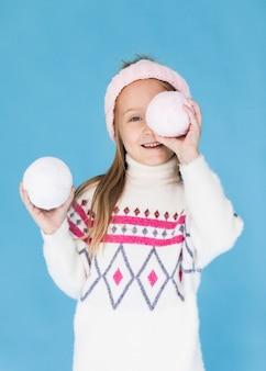 Белокурая маленькая девочка закрыла лицо снежком