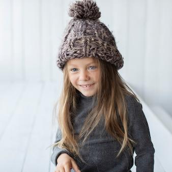 Портрет улыбающегося маленькая девочка в шляпе зимой