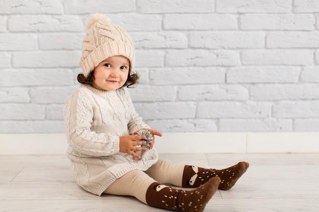 Милая маленькая девочка держит шишка