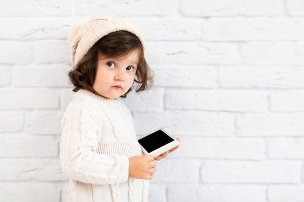 Милая маленькая девочка держит телефон