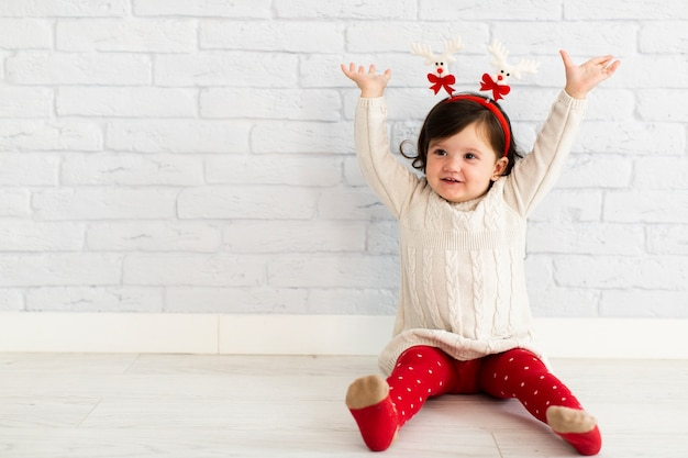 Счастливая маленькая девочка поднимает руки