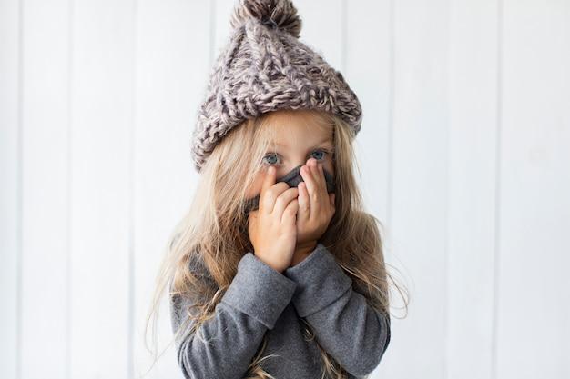 彼女の顔を覆っている面白いブロンドの女の子