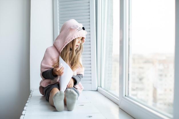 Вид спереди очаровательны маленькая девочка, глядя на окна