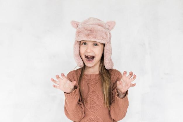Улыбающаяся маленькая девочка делает смешные рожи