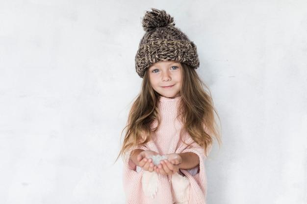 Модно одетая маленькая девочка смотрит на фотографа