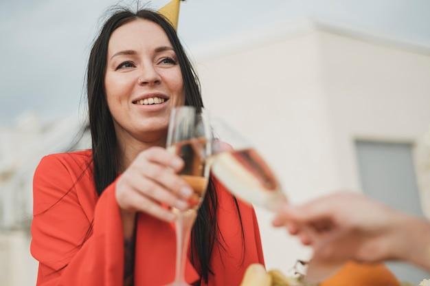 Красивая женщина в красном платье поднимает бокал шампанского