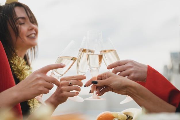 Счастливые девушки поднимают бокалы с шампанским