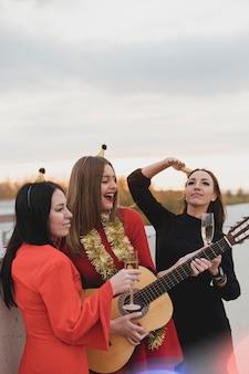 屋上パーティーでギターを弾く女性のグループ