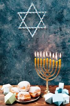 テーブルの上のキャンドルホルダーとユダヤ人のお菓子