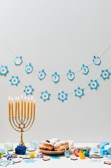 テーブルの上にお菓子とヘブライ語の本枝の燭台