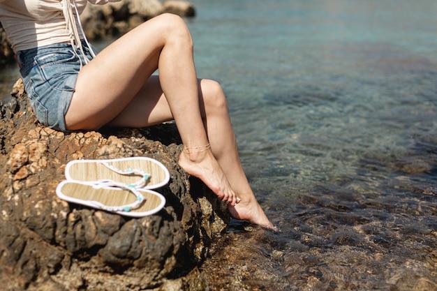 水の背景を持つ女性の足