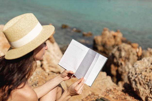 ノートブックを閲覧して帽子を持つ若い女性