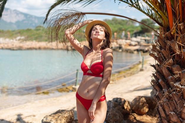ヤシの木の近くの帽子を持つ美しい女性
