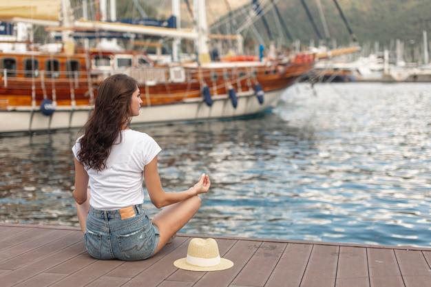 港の海岸に座っているブルネットの女性