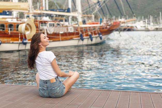 港の海岸に座っているかわいい女性