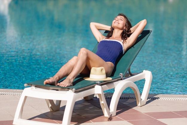 Молодая женщина сидит на шезлонге на краю бассейна